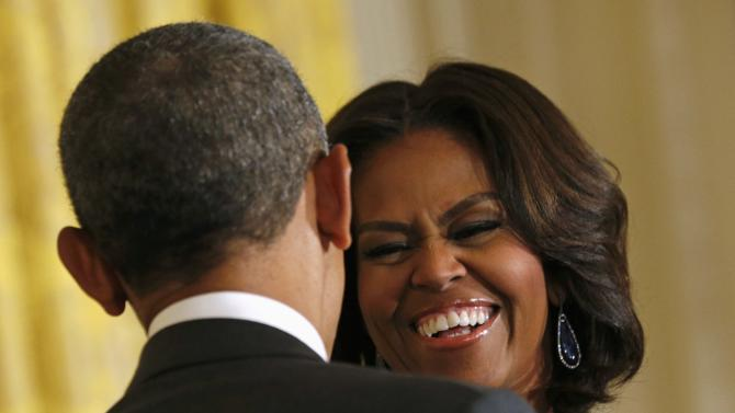"""First lady Michelle Obama smiles back at U.S. President Barack Obama during the announcement of the  """"Let Girls Learn"""" initiative at the White House"""