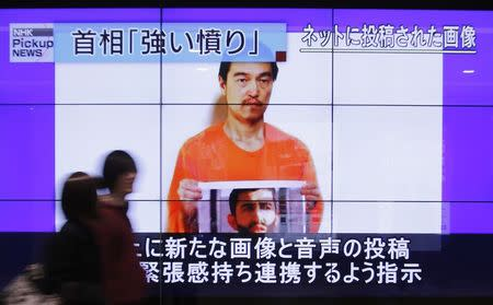 People walk past television screens displaying a news program, about an Islamic State video showing Japanese captive Kenji Goto, in Tokyo