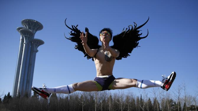 A participant jumps as he poses for photographers before running in the half-naked marathon at a park in Beijing