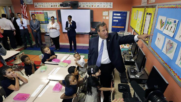 New Jersey Gov. Chris Christie looks at art work as he visits students at Octavius V. Catto Community Family School Tuesday, Sept. 9, 2014, in Camden, N.J. Later, speaking at a news conference in Camden, Christie said the state government would have no role in either regulating or taxing sports books. He also said he would not encourage or discourage casinos or racetracks to get into the business. On Monday, Christie nevertheless announced a directive that sports betting was no longer illegal in the state, so long as it's not sponsored by the state government. His administration also filed a request with a judge to say that the action is legal. (AP Photo/Mel Evans)