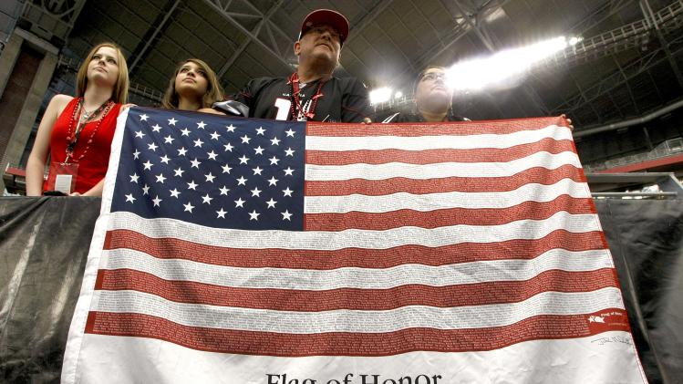 Joel Soderburg, third from left, daughter Marissa Soderburg, 17, left, daughter  Delores Soderburg, second from left , and daughter Jessica Soderburg, 17,  right, hang a flag with the names of those lost 10 years ago before an NFL football game between the Arizona Cardinals and the Carolina Panthers, Sunday, Sept. 11, 2011, in Glendale, Ariz. (AP Photo/Ralph Freso)