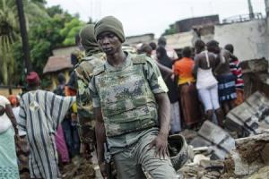 Soldiers stand on the remains of a house that was burnt down during pre-election communal violence in the Taouyah neighbourhood of Guinea's capital Conakry