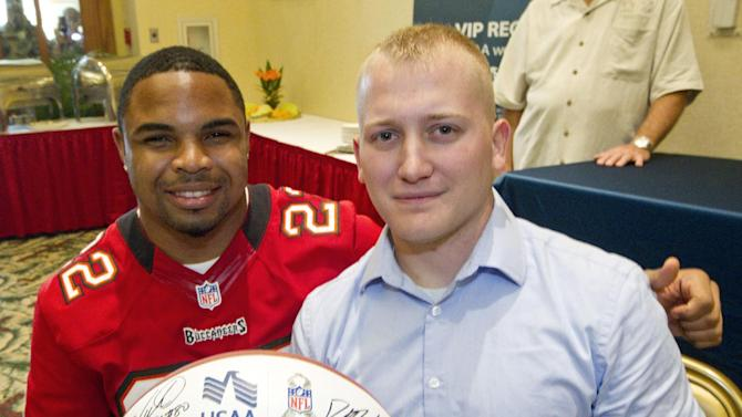 IMAGE DISTRIBUTED FOR USAA - Tampa Bay Buccaneers running back Doug Martin (22) poses for a picture with Zackary Newbury, a former member of the Warrior Transition Battalion now on active duty with the United States Army, at Schofield Barracks Thursday, Jan. 24, 2013, in Honolulu. Six National League Football players met with members of the Warrior Transition Battalion. The football players signed autographs and learned about the various United States Army servicemen who where wounded in the war in Iraq and Afghanistan. (Eugene Tanner/AP Images for USAA)
