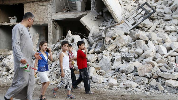 People walk past the rubble of collapsed buildings during the Eid al-Fitr festival in Maarat Al-Nouman, south of Idlib