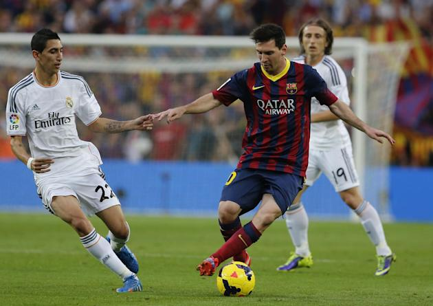 Barcelona's Lionel Messi from Argentina controls the ball past Real Madrid's Angel Di Maria from Argentina during a Spanish La Liga soccer match between Barcelona F.C. and Real Madrid at the Camp Nou