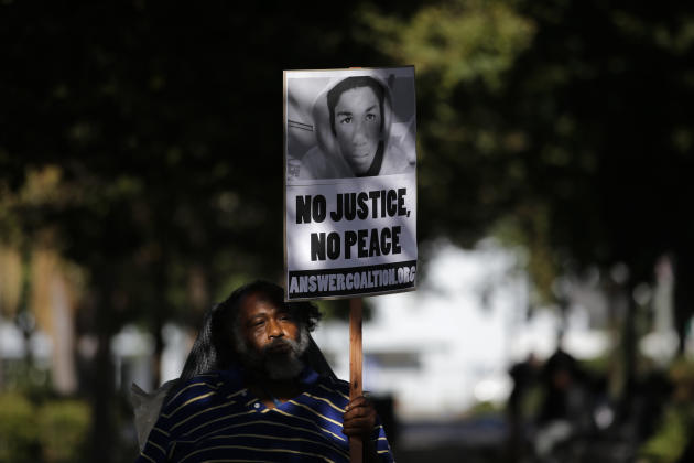 John Simpson, 56, carries a sign showing an image of Trayvon Martin during a demonstration in reaction to the acquittal of neighborhood watch volunteer George Zimmerman on Monday, July 15, 2013, in Lo