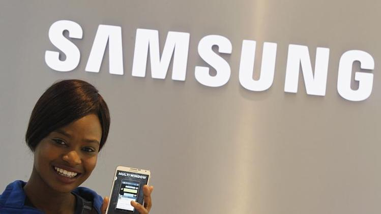 A Samsung employee holds a mobile phone at a Samsung display store in Johannesburg