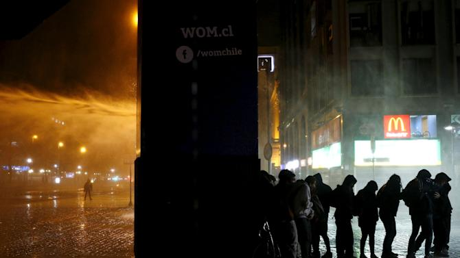 Mapuche Indian activists take cover from a jet of water released from a riot police vehicle, while a group of truck owners protest against what they claim is damage done by other Mapuche Indians towards their property, in Santiago