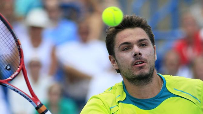 Stanislas Wawrinka, from Switzerland, hits a volley against Roger Federer, from Switzerland, during a semifinal match at the Western & Southern Open tennis tournament, Saturday, Aug. 18, 2012, in Mason, Ohio. (AP Photo/Al Behrman)