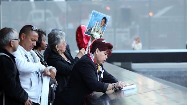 Rosario Tejada, right, of Columbia makes as rubbing of the name of her nephew, Wilder Gomez, of the Queens borough of New York, who died in the north tower of the World Trade Center. She is attending the observances held on the eleventh anniversary of the attacks on the World Trade Center, in New York, Tuesday Sept. 11, 2012.  (AP Photo/The Record, Chris Pedota, Pool)