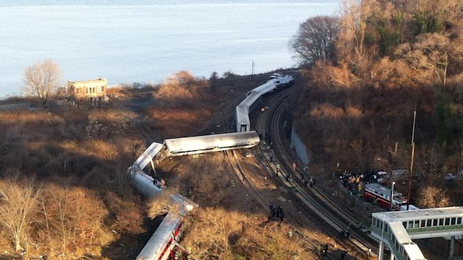 """Cars from a Metro-North passenger train are scattered after the train derailed in the Bronx neighborhood of New York, Sunday, Dec. 1, 2013. The Fire Department of New York says there are """"multiple injuries"""" in the train derailment, and 130 firefighters are on the scene. Metropolitan Transportation Authority police say the train derailed near the Spuyten Duyvil station. (AP Photo/Edwin Valero)"""