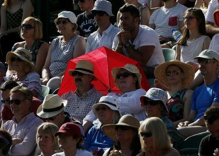 A couple shelter from the sun with a red umbrella at the Wimbledon Tennis Championships in London