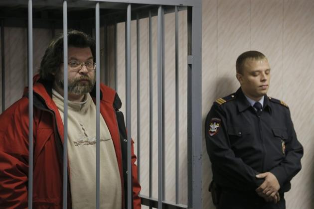 A police officer guards a cage with Greenpeace activist Roman Dolgov, left, in a court room in Murmansk, Russia, on Thursday, Sept. 26, 2013. A Russian court on Thursday jailed Greenpeace arctic proje