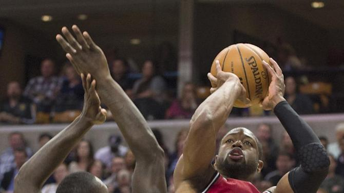 Miami Heat's Dwyane Wade (3) gets a shot off over the defense of Indiana Pacers' Lance Stephenson (1) during the first half of an NBA basketball game in Indianapolis, Friday, Feb. 1, 2013. (AP Photo/Doug McSchooler)