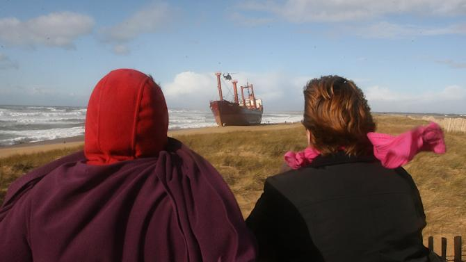 People look at a helicopter hovering above the decks of the cargo ship TK Bremen which is stranded on Kerminihy beach at Erdeven, near Lorient, France, Friday, Dec. 16, 2011. High winds have beached the cargo ship off France's Atlantic coast and some of the 220 tons of fuel in its hold is leaking, threatening a local beach. (AP Photo/David Vincent)