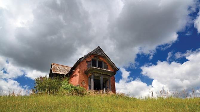 """This photo provided by Troy Larson shows an abandoned house in Sims, N.D., and is featured on the cover of the book """"Ghosts of North Dakota Volume 2,"""" which documents ghost towns throughout the state. (AP Photo/Troy Larson)"""