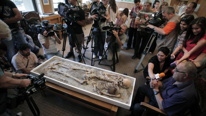 Journalists put questions to the National History Museum's director Bozhidar Dimitrov, right in Sofia, as they surround  a a displayed skeleton dating back to the Middle Ages and recently unearthed in the black sea town of Sozopol, at National History Museum in  Sofia, Thursday, June 14, 2012. Ever since archaeologists announced last week that they had found two ancient skeletons in Bulgaria with iron rods thrust through their chests, the media have been reporting how Bulgarians once did that to prevent the dead from emerging from the grave as vampires. On Saturday, one of those 700-year-old skeletons will be put on display at the National History Museum in Sofia, and its director, Bozhidar Dimitrov, says he expects there to be a big turnout. (AP Photo/Valentina Petrova)