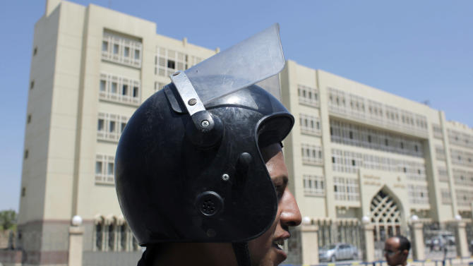 An Egyptian riot police officer secures the court house complex, during the trial session of three Mubarak-era ministers, who were later acqitted, at the Supreme State Security Court in Cairo, Egypt Tuesday, July 5, 2011. An Egyptian court has acquitted three Mubarak-era ministers of corruption charges while finding a fourth guilty in absentia. (AP Photo/Nasser Nasser)