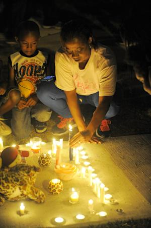 In this Wednesday, July 30, 2014 photo, Mary Lindsey, of Detroit, lights a candle near several stuffed animals, at a vigil for Jakari Pearson, who died from a gunshot wound, at the New Brewster Projects in Detroit's east side. Pearson was sleeping in his upstairs bedroom when a bullet entered through a window and struck him in the chest. (AP Photo/Detroit News, Steve Perez)
