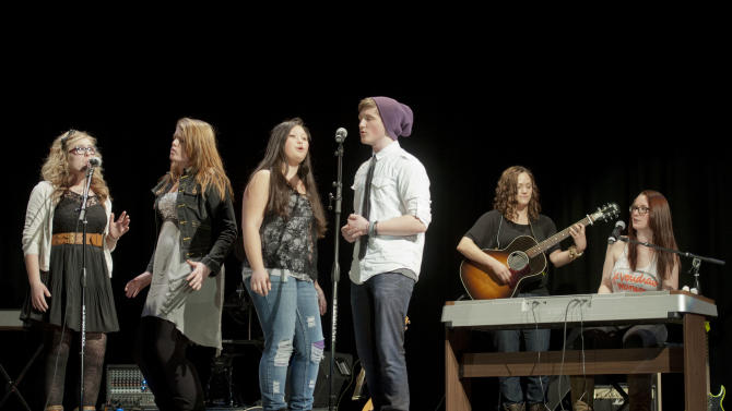 """IMAGE DISTRIBUTED FOR VH1 - Ingrid Michaelson and Allie Moss perform with students from Streetsboro High School during the VH1 Save the Music Foundation We Are All """"Blood Brothers"""" event on Tuesday, Feb., 26, 2013 in Streetsboro, Ohio. (Photo by Jason Miller/Invision for VH1/AP Images)"""