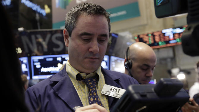 FILE - In this Friday, March 28, 2014, file photo, Trader Daniel Trimble, left, works on the floor of the New York Stock Exchange. (AP Photo/Richard Drew, File)