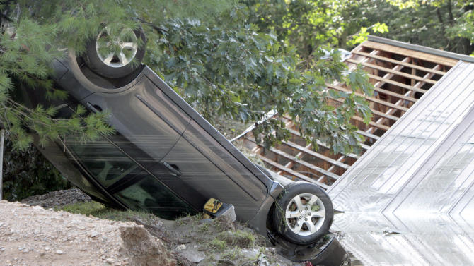 A car lies upside down in the aftermath of Tropical Storm Irene on Monday, Aug. 29, 2011 in Waterbury, Vt. (AP Photo/Toby Talbot)