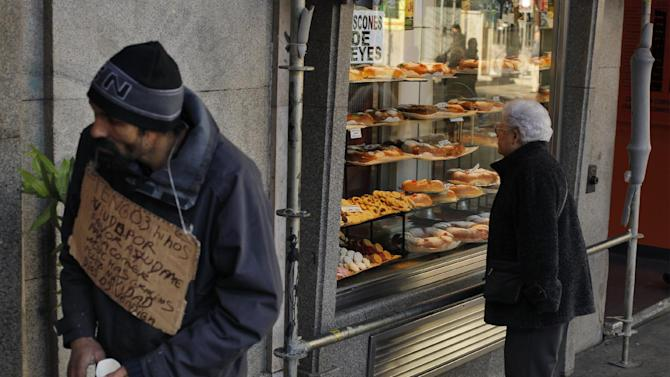 """A man begs money with a banner reading """"I have three kids, help me please, thank you, happy christmas, god bless you"""" as a woman looks at  'Three Kings' cakes outside  a bakery shop in Madrid, Sunday, Jan. 6, 2013. (AP Photo/Andres Kudacki)"""