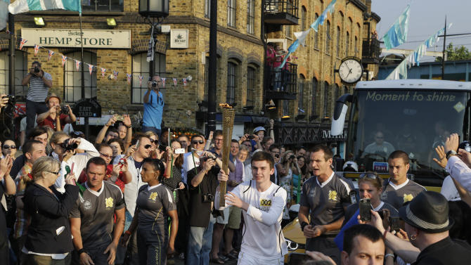 Torchbearer Darren Fitzpatrick carries the Olympic Flame through the streets of Camden in London, ahead of the 2012 Summer Olympics, Thursday, July 26, 2012, The Olympic Torch was carried around England in a relay of torchbearers to make its way to the opening ceremony on Friday. (AP Photo/Lefteris Pitarakis)