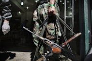 A Syrian rebel holds AK-47 rifles belonging to wounded comrades at the entrance to a hospital in the Sheikh Fares district of the northern city of Aleppo on September 18. The new UN envoy on children in conflict, Leila Zerrougui, said the world body is investigating Syrian rebel groups as well as government forces for attacks that have killed children