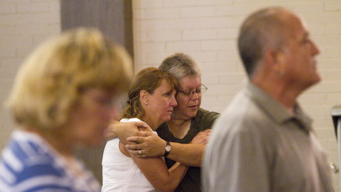 "Judy Goos, left, is embraced by her friend Lisa Stevens at the Grant Avenue United Methodist Church in Aurora, Colo. on Sunday, July 22, 2012, two days after a shooting rampage at a midnight showing of ""The Dark Knight Rises"" Batman movie. She arrived minutes after the shooting since her daughter Emma Goos, 19, was in theater nine and called her right after she called 911. Her husband is the pastor of the church. (AP Photo/Barry Gutierrez)"