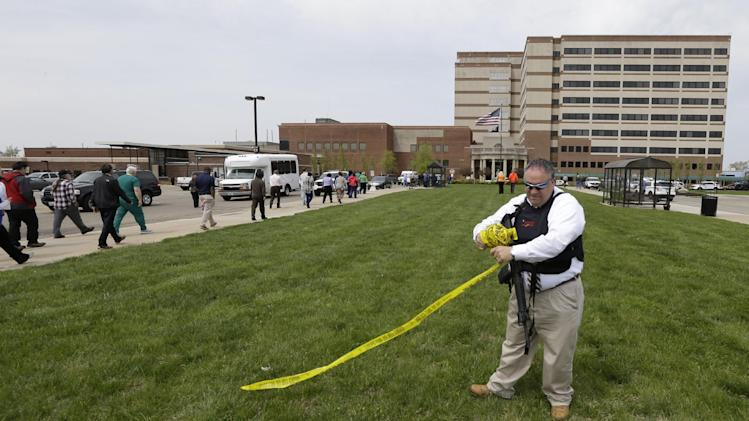 A police official takes down yellow police tape outside a Veterans Affairs hospital after telling people who were evacuated they could reenter the building, Monday, May 5, 2014, in Dayton, Ohio. A city official says a suspect is in police custody after a shooting at the Veterans Affairs hospital that left one person with a minor injury. (AP Photo/Al Behrman)