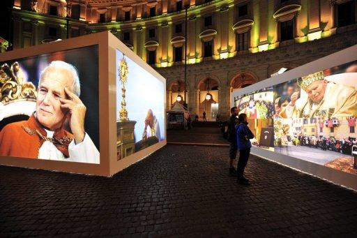 "Large photos of Pope John Paul II are seen displayed in central Rome, on April 29. Hundreds of thousands of pilgrims are expected to descend on the Italian capital for Sunday's beatification, which will confer a ""blessed"" status on the charismatic pope, who died in 2005 after reigning for nearly 27 years"