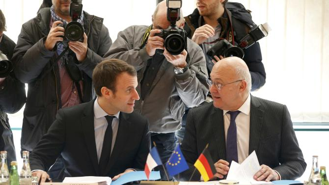 French Economy Minister Emmanuel Macron and French Finance Minister Michel Sapin attend a meeting at the Bercy Finance Ministry in Paris, France