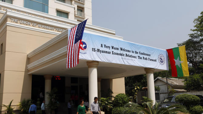 """National flags of Myanmar, right, and the United States decorate the entrance with a banner marking the conference titled """"U.S.-Myanmar Economic Relations: The Path Forward"""" at the Union of Myanmar Federation of Chambers of Commerce and Industry (UMFCCI) office Monday, Feb. 25, 2013, in Yangon, Myanmar. Flanked by small national flags, Win Aung, the president of the UMFCCI, Myanmar's main business association, and U.S. Assistant Secretary of State Jose Fernandez shook hands in Yangon Monday and agreed to deepen business ties between their two countries. (AP Photo/Khin Maung Win)"""