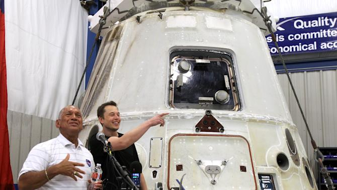 NASA Administrator Charles Bolden, left, and SpaceX CEO Elon Musk, right, answer questions in front of the SpaceX Dragon spacecraft Wednesday June 13, 2012 at the SpaceX Rocket Development Facility in McGregor, Texas. The spacecraft recently made history as the first commercial vehicle to visit the International Space Station. The California-based SpaceX is the first private business to send a cargo ship to the space station. (AP Photo/Waco Tribune-Herald, Duane A. Laverty)