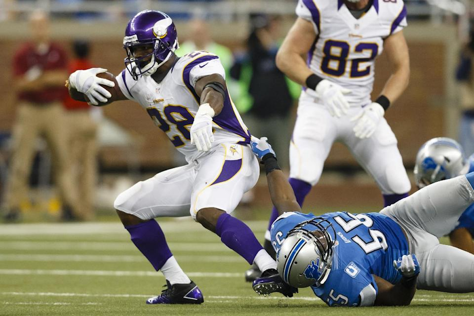 Minnesota Vikings running back Adrian Peterson (28) drags Detroit Lions middle linebacker Stephen Tulloch (55) as he runs the ball during the second half at Ford Field in Detroit, Sunday, Sept. 30, 2012. (AP Photo/Rick Osentoski)