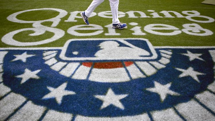 Los Angeles Dodgers' A.J. Ellis walks past the Major League Baseball logo painted on the field before a season-opening baseball game between the Los Angeles Dodgers and the San Francisco Giants in Los Angeles, Monday, April 1, 2013. (AP Photo/Jae C. Hong)