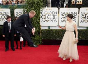 Zooey Deschanel reacts to Jesse Tyler Ferguson jumping at the the 71st annual Golden Globe Awards in Beverly Hills