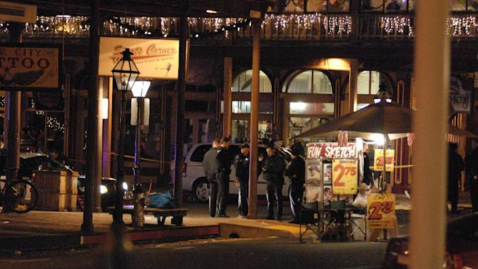 In this image provided by Robert Petersen police inspect the scene of a shooting outside the Sports Corner Cafe in Sacramento Calif. Monday Dec. 31, 2012. Police say two people died and three others were injured in a New Year's Eve shooting after a fight in a restaurant in the Old Sacramento area. After the shooting, police decided to cancel the area's midnight fireworks show, which were part of the New Year's Eve celebration. (AP Photo/Robert Petersen)