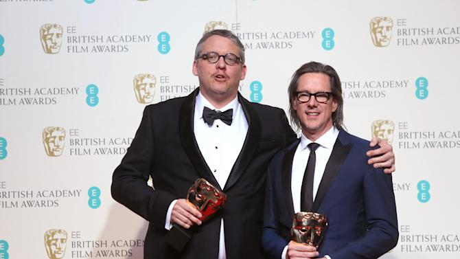 Adam McKay, left, and Charles Randolph hold their awards for Best Adapted Screenplay for the film 'The Big Short' backstage at the BAFTA 2016 film awards at the Royal Opera House in London, Sunday, Feb. 14, 2016. (Photo by Joel Ryan/Invision/AP)