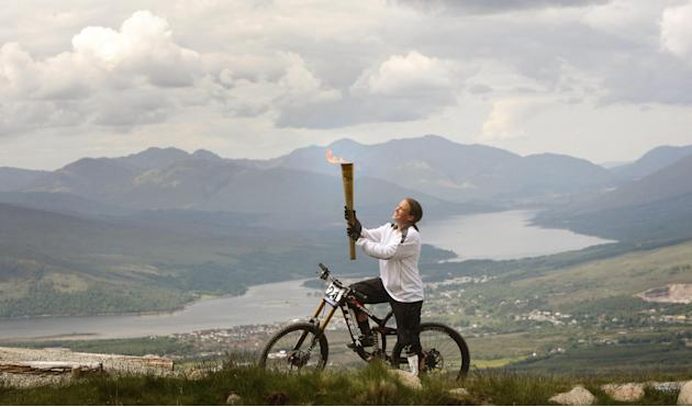 This image made available by LOCOG shows Mountain Biker Tracy Moseley carries the Olympic Flame on the Nevis Range, a mountain ski resort in the The Highlands of Scotland near Ben Nevis and Fort Willi