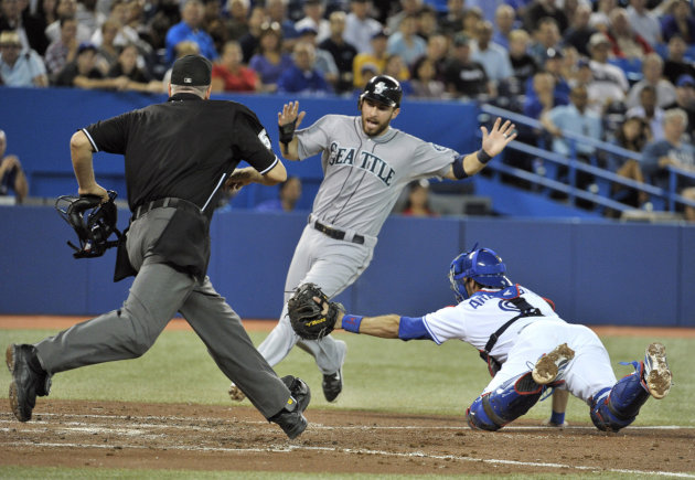 Mariners base runner Ackley scores a run ahead of the tag by Blue Jays catcher Arencibia during their MLB American League baseball game in Toronto