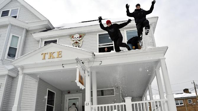 From left, Worcester Polytechnic Institute freshmen Kyle Foster and Steven Como, both members of the Tau Kappa Epsilon fraternity, jump from the fraternity house porch roof into a steep snow bank on Wachusett Street in Worcester, Mass., in the aftermath of an overnight storm on Saturday, Feb. 9, 2013. (AP Photo/Worcester Telegram & Gazette, Paul Kapteyn)