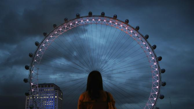 A woman watches as The EDF Energy London Eye is lit up on July 19, 2012 in London, England. The giant ferris wheel will be lit up with different coloured lights to reflect Tweets posted about the London 2012 Olympic Games. (Photo by Peter Macdiarmid/Getty Images)