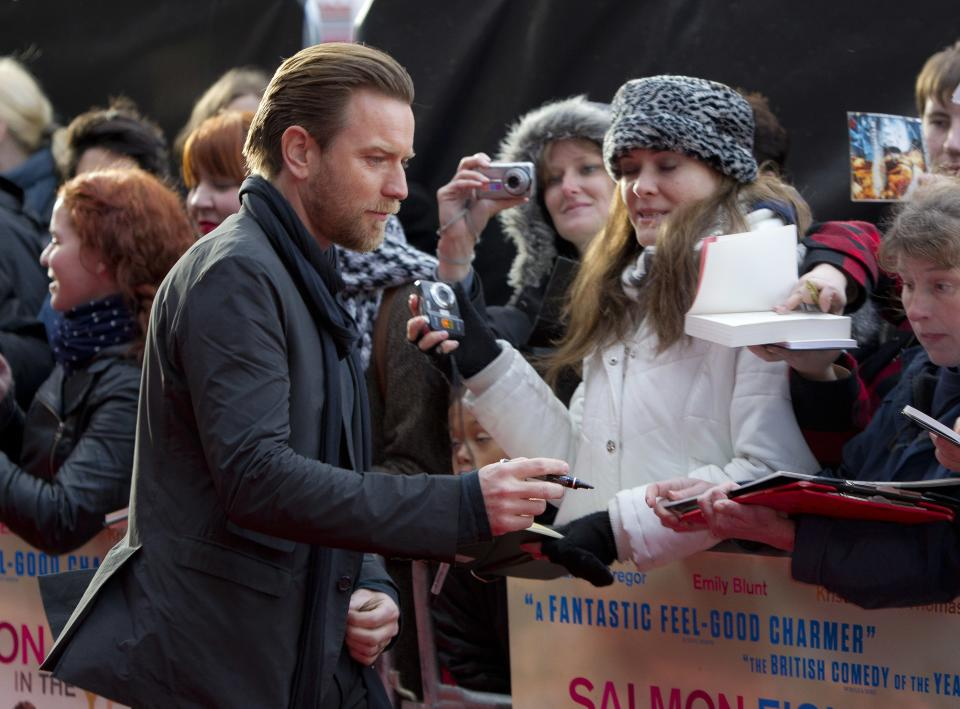 Actor Ewan McGregor signs autographs for fans as he arrives at the 'Salmon Fishing In The Yemen' European premiere at a west London cinema, Tuesday, April 10, 2012. (AP Photo/Joel Ryan)
