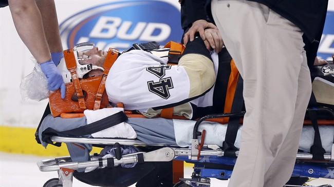 Pittsburgh Penguins' Brooks Orpik is taken off the ice after being injured in the first period of an NHL hockey game against the Boston Bruins in Boston, Saturday, Dec. 7, 2013. (AP Photo/Michael Dwyer)