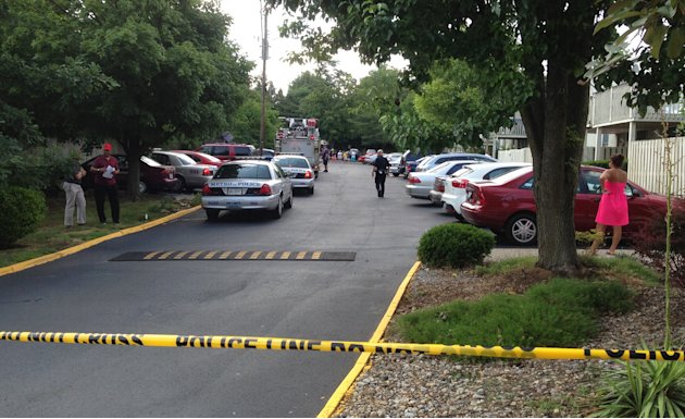 Police tape ropes off area at Lakeview Condominiums, where three people were shot to death and a fourth was seriously injured at a condominium building Wednesday, June 19, 2013 in Louisville, Ky. (AP