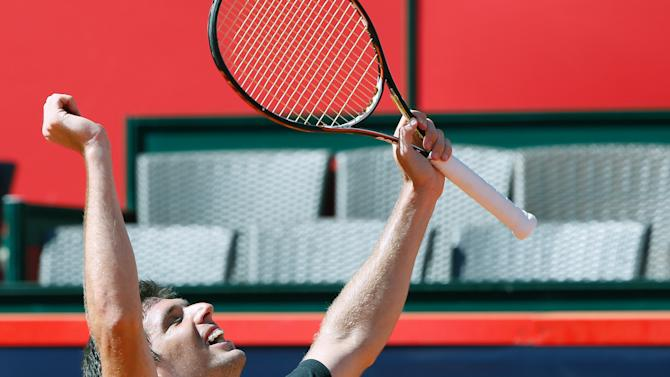 Argentina's Federico Delbonis celebrates his victory after he won the semifinal match against Switzerland's Roger Federer at the bet-at-home German Open ATP tennis tournament inHamburg,Germany, Saturday July 20, 2013. (AP Photo/dpa,Axel Heimken)