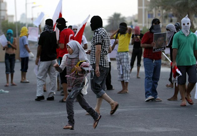 A Bahraini girl crosses the street in the midst of masked anti-government protesters in Sitra, Bahrain, Wednesday, Aug. 31, 2011, hours after the death of 14-year-old Sitra protester Ali Jawad Ahmad. Bahraini security forces clashed with anti-government protesters after Wednesday morning prayers, and the teenager died after being hit by a police tear gas canisters, human rights activists said. (AP Photo/Hasan Jamali)