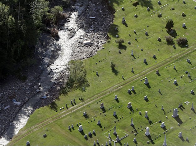 Damage to the cemetery with uncovered coffins is seen in this aerial view on Tuesday, Aug. 30, 2011 in Rochester, Vt.  National Guard helicopters rushed food and water Tuesday to a dozen Vermont towns